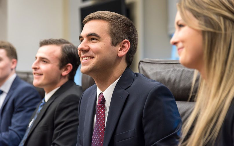 Pitt Business students smiling at a conference room table