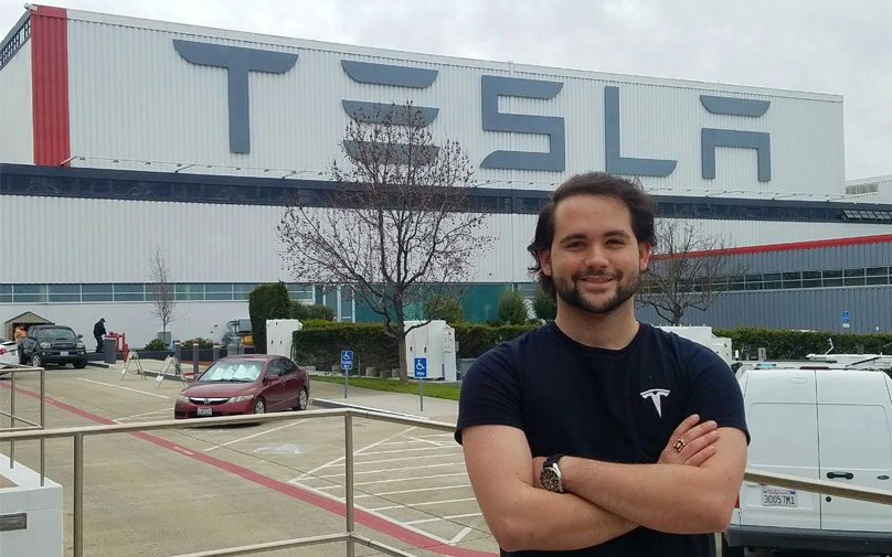 Student poses in front of Tesla facility buildilng