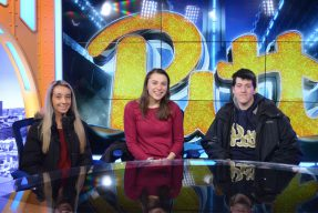 Pitt students behind the desk of the Pitt athletics sports studio space