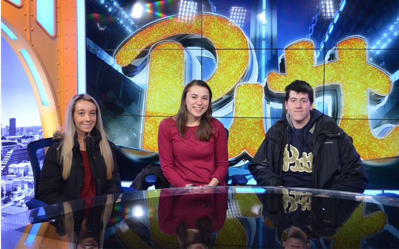 Pitt students behind the desk of the Pitt athletics sports studio space