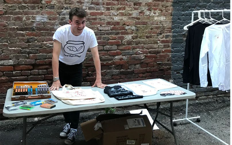 Student Connor Murray selling cassette tapes and merchandise at a table