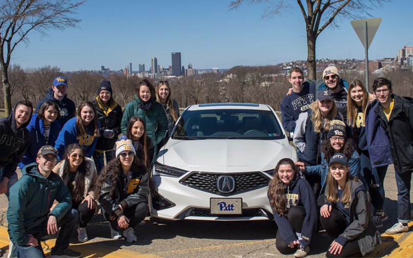 Students pose in front of the Acura car with the City of Pittsburgh in the background