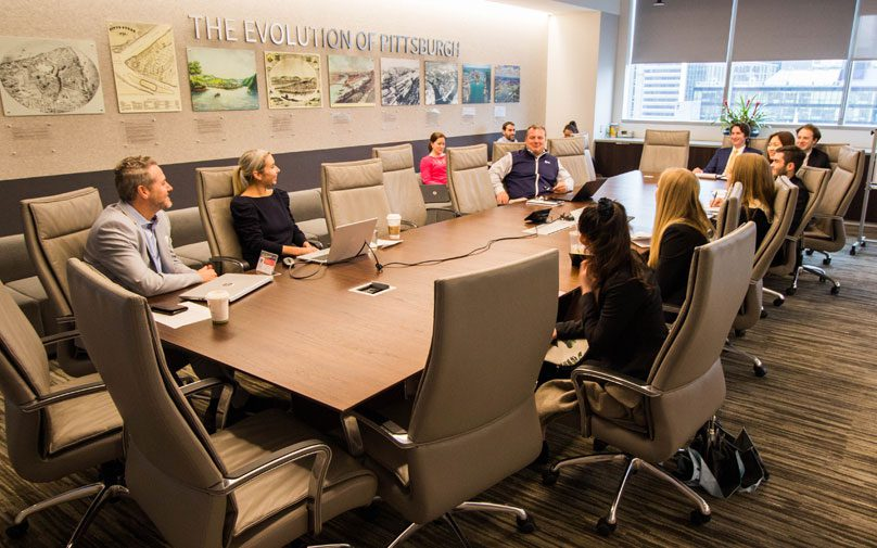 Students and employees of JLL gather around the conference room table for a session.