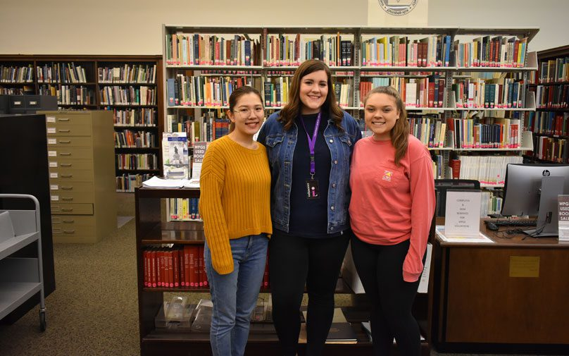 Student tax volunteers pose in front of the library stacks
