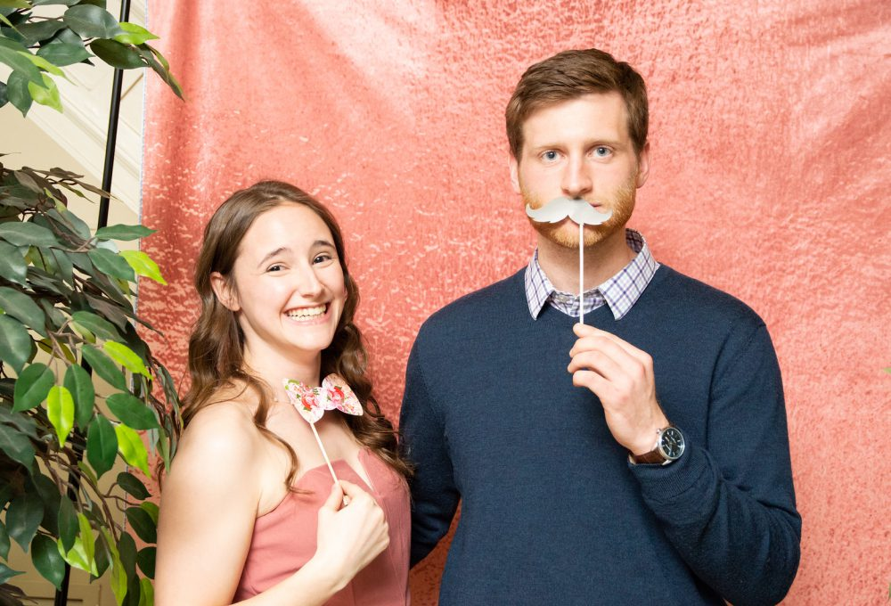 A boy and a girl stand together in the photo booth