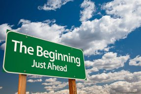 The beginning, just ahead sign with blue sky and clouds